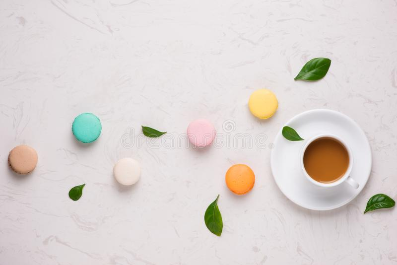 Tea time flat lay. Cup of coffee and colorful macaroons on the w royalty free stock image