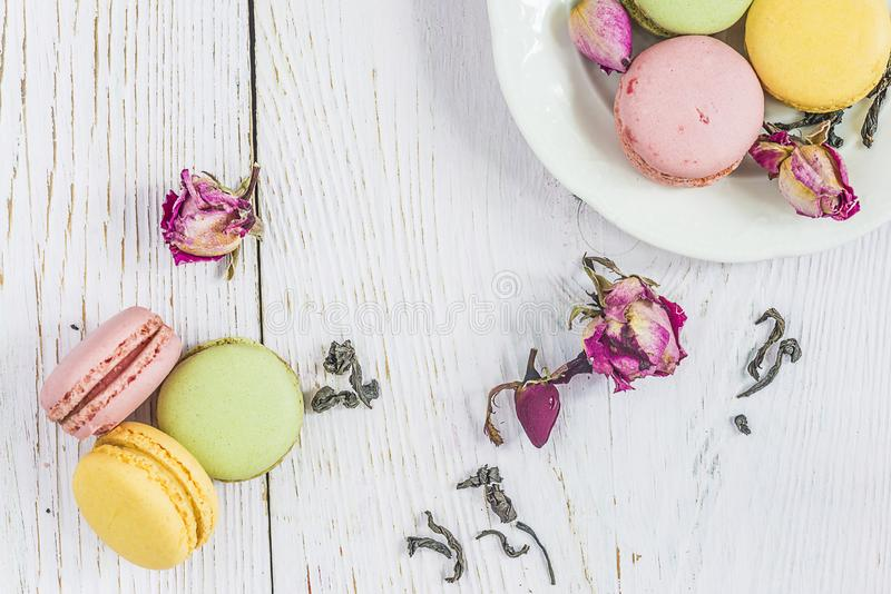 Tea time with french macaroons: traditional french macaroons, dry tea, rose buds. On the white paint wooden background top view stock image