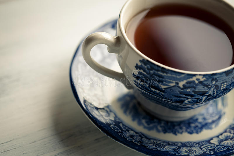 Tea Time. Photo of tea in an old fashioned porcelain cup on wooden board