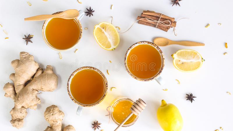 Preventing colds with vitamins. Tea with turmeric among products for improving immunity and treating colds - ginger, lemon, honey, anise. Top view, flat lay royalty free stock photos