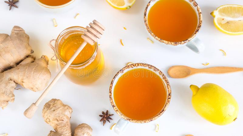 Preventing colds with vitamins. Tea with turmeric among products for improving immunity and treating colds - ginger, lemon and a jar of honey with a wooden spoon stock image