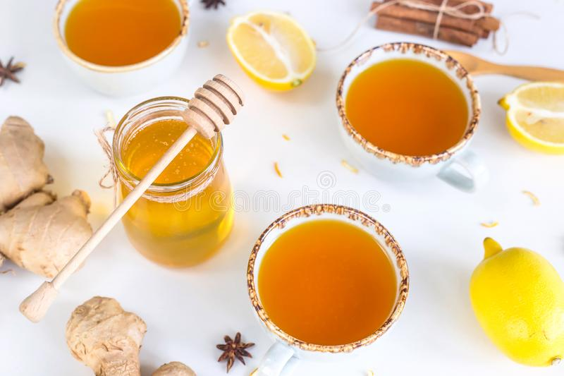 Preventing colds with vitamins. Tea with turmeric among products for improving immunity and treating colds - ginger, lemon and a jar of honey with a wooden spoon royalty free stock images
