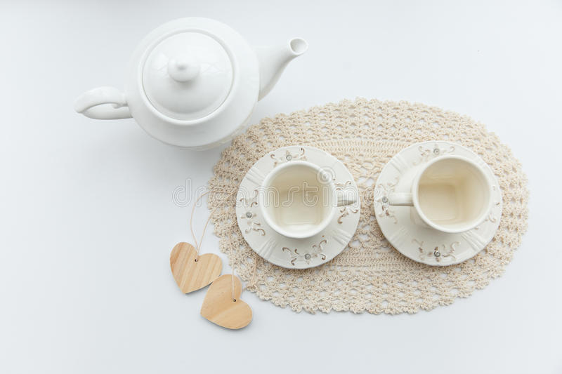 Tea for two. Two white cups of tea with two hearts and kettle. royalty free stock image