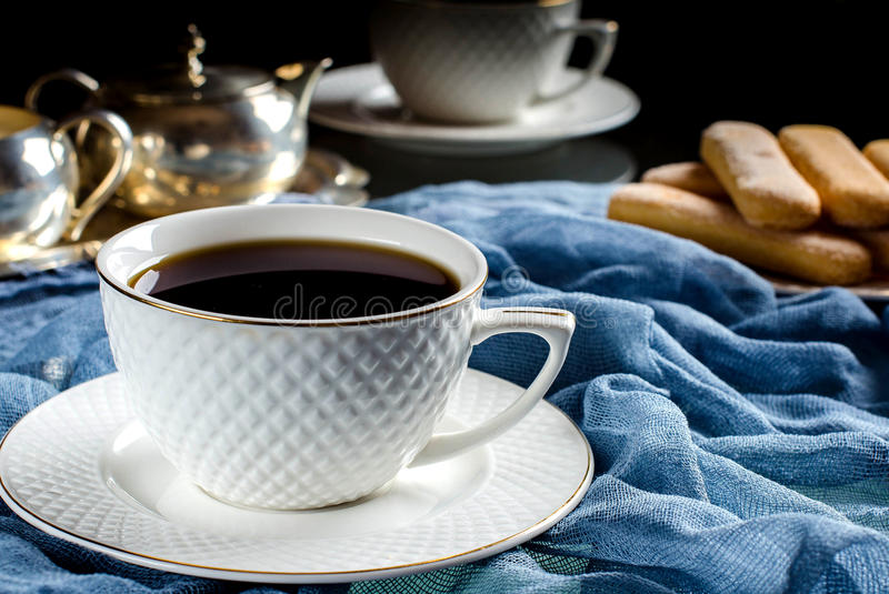 Tea in a white Cup. A dark photo. Fragrant hot tea. Beautiful white Cup with a saucer. The background of blue cloth. Tea with biscuits. Silverware. A dark photo royalty free stock image