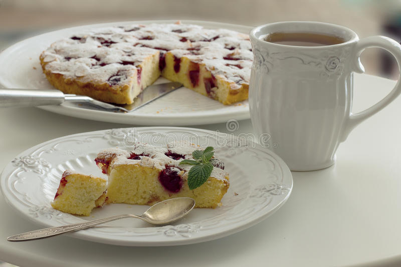 Tea in a white mug, a piece of cherry pie on a white plate. Horizontal photo. Tea in a white mug, a piece of cherry pie on a white plate on a white table in a stock photos