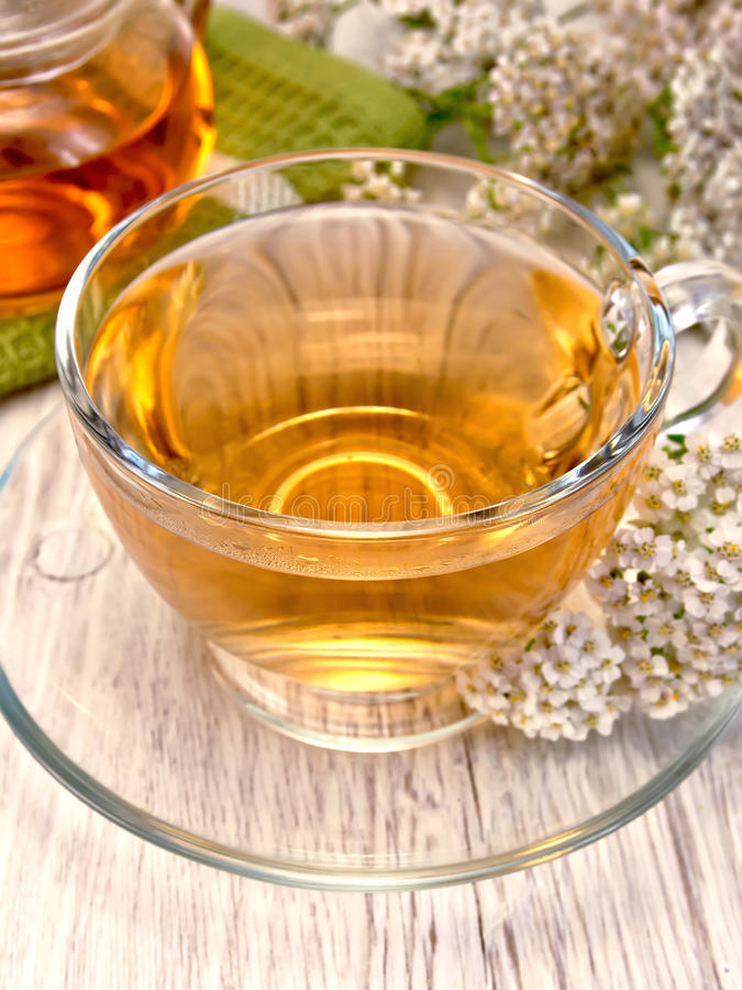 Tea with yarrow in glass cup on board royalty free stock photography