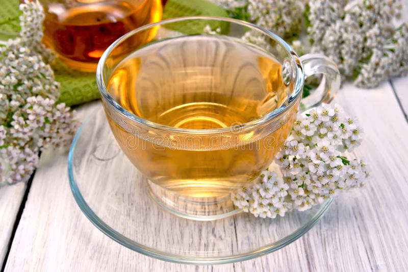 Tea with yarrow in glass cup on light board royalty free stock photo