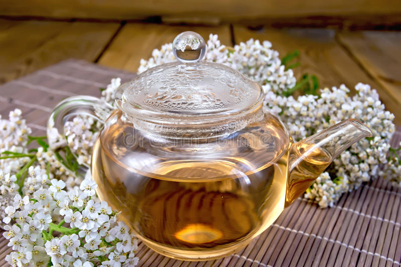Tea with yarrow in glass teapot on bamboo royalty free stock photo