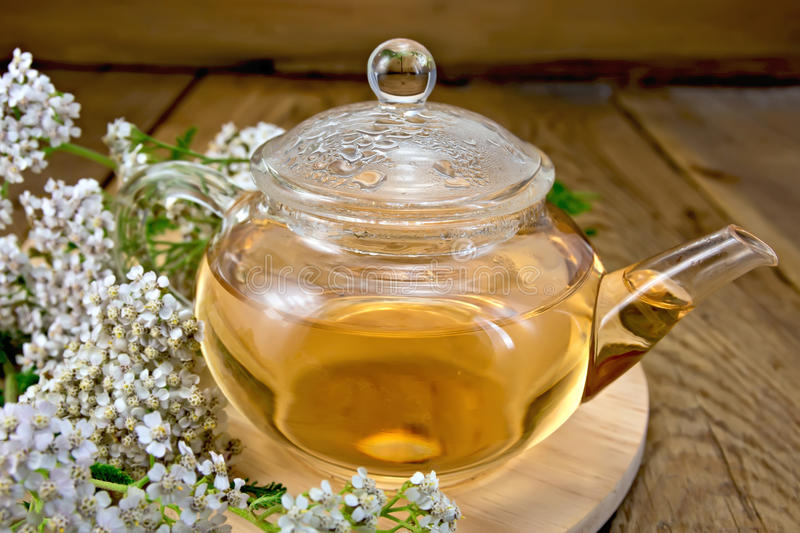 Tea with yarrow in glass teapot on board royalty free stock photos