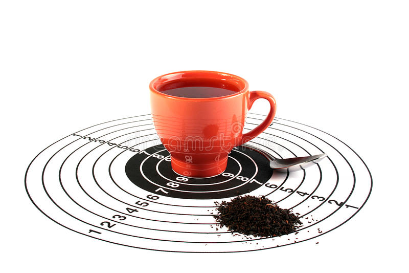 Tea is your choice. The red cup with tea is in the centre of a target for accuracy training, nearby there is a teaspoon and tea leaves are scattered. The royalty free stock image