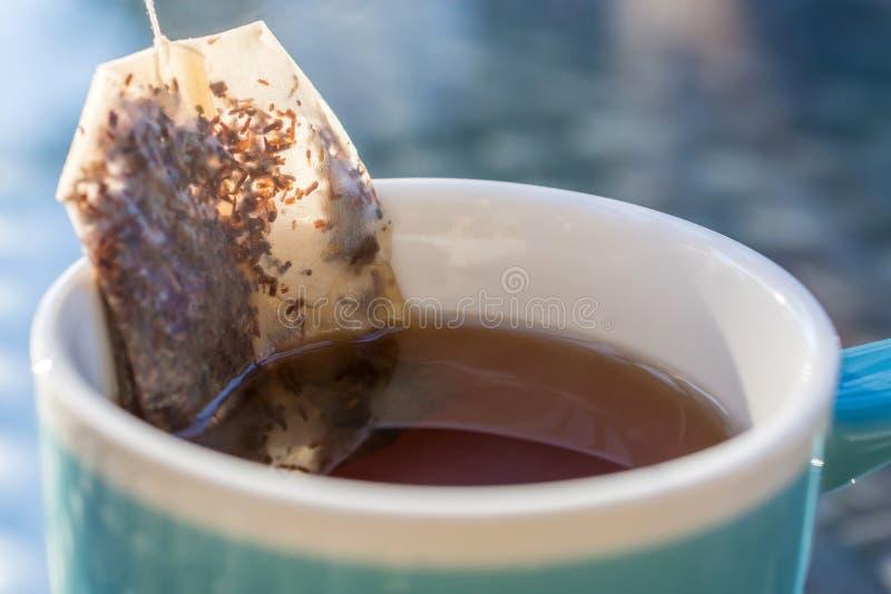 Teabag με το βοτανικό τσάι σε ένα φλυτζάνι στοκ φωτογραφία