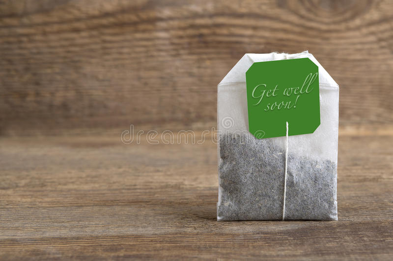 Teabag on wooden background, get well soon stock photo