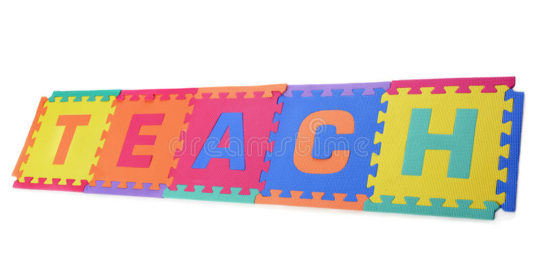 Teach!. A colorful floor puzzel of letters put together to spell the word teach. Isolated on white stock image