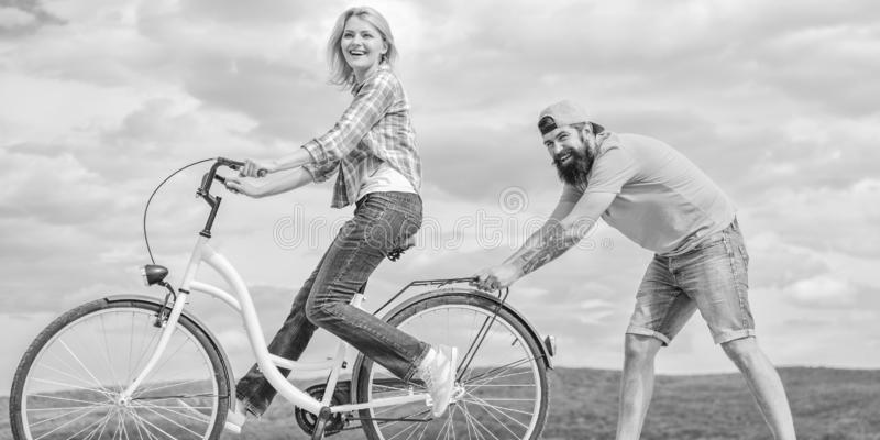 Teach adult to ride bike. Find balance. Woman rides bicycle sky background. How to learn to ride bike as an adult. Girl royalty free stock photography