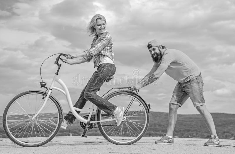 Teach adult to ride bike. Man helps keep balance and ride bike. Find balance. Woman rides bicycle sky background. How to royalty free stock photos
