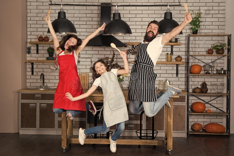 Teach kid cooking food. Weekend breakfast. Cooking with child might be fun. Having fun in kitchen. Family mom dad and. Little daughter wear aprons jump in royalty free stock photos