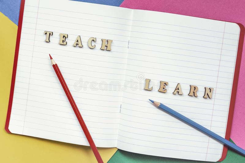 Teach and learn, words in open notebook, colored paper sheets. Concept of education, starting school, back to school stock photos