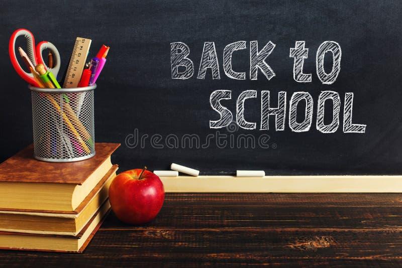 Teacher' стол s с материалами сочинительства, книгой и яблоком, пробелом для текста или предпосылкой для темы школы r стоковые изображения