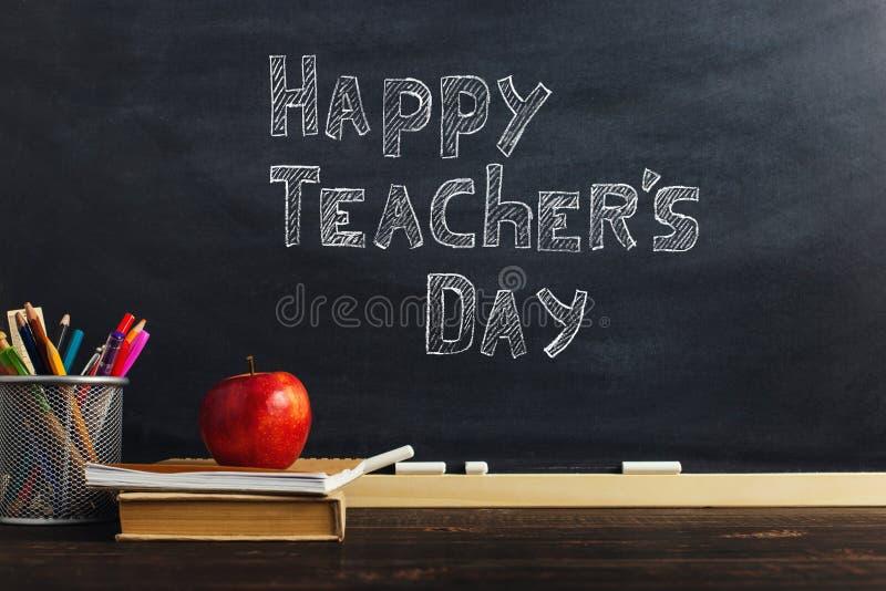 Teacher' стол s с материалами сочинительства, книгой и яблоком, пробелом для текста или предпосылкой для темы школы r стоковое фото