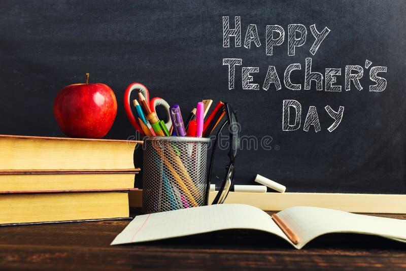 Teacher' стол s с материалами сочинительства, книгой и яблоком, пробелом для текста или предпосылкой для темы школы r стоковое изображение