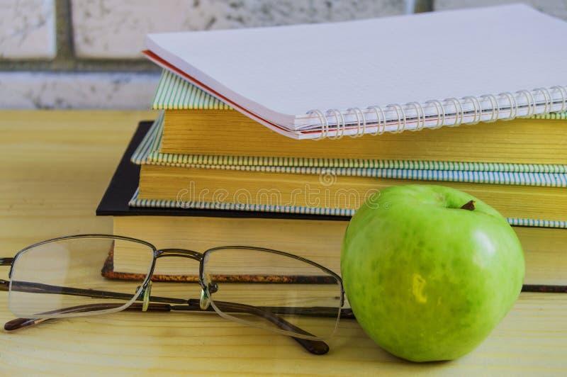 Teacher';s天概念和回到学校、绿色苹果计算机、书、膝上型计算机、放大镜和笔在木桌,阳光上 库存图片