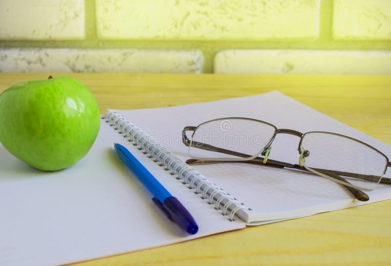 Teacher';s天概念和回到学校、绿色苹果计算机、书、膝上型计算机、放大镜和笔在木桌,阳光上 免版税库存图片