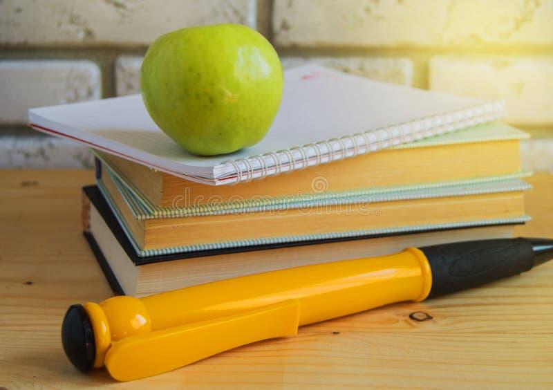 Teacher';s天概念和回到学校,绿色苹果计算机,在书和笔记本,阳光的大纪念品笔 免版税库存图片