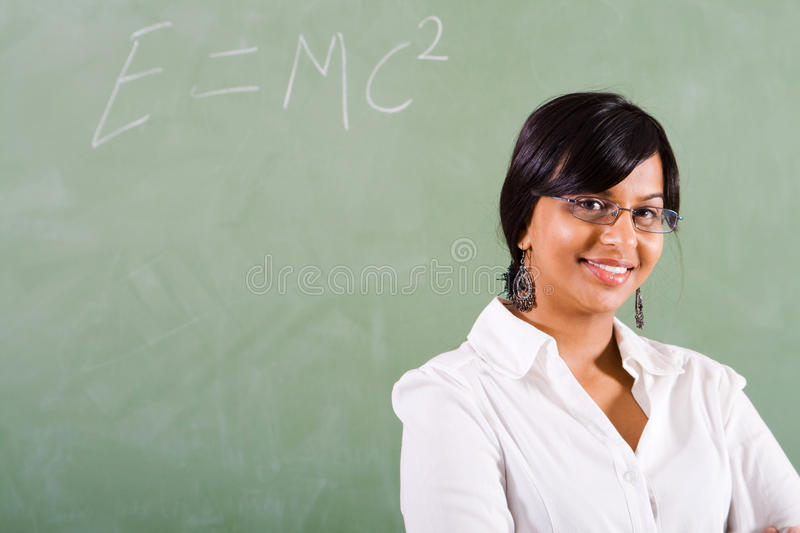 Teacher. Beautiful young school teacher standing in front of chalkboard royalty free stock photos