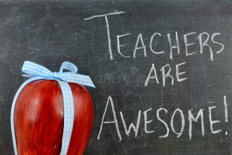 Teacher appreciation image of a red apple tied up with a cute blue ribbon stock image