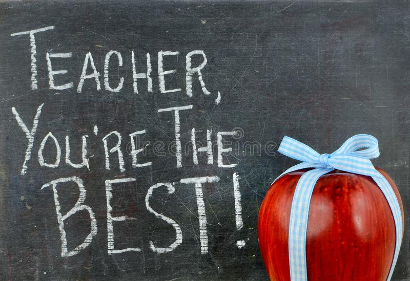 Teacher appreciation image of a red apple tied up with a cute blue ribbon. In front of a worn blackboard with a message written in white chalk stock photo