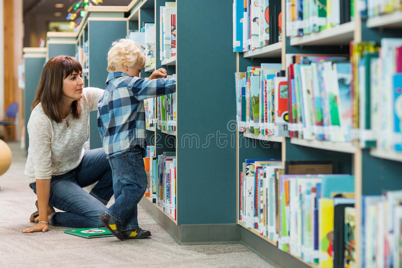 Teacher Assisting Boy In Selecting Book From royalty free stock photography