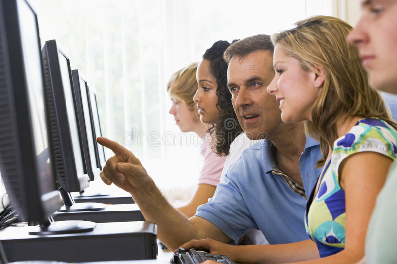 Teacher assisting college student in computer lab royalty free stock images