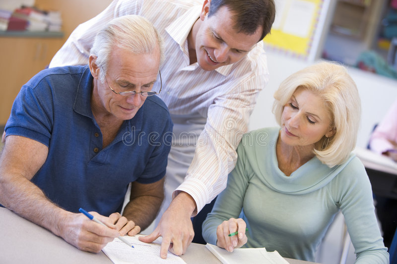 Teacher assisting mature students in class royalty free stock photography