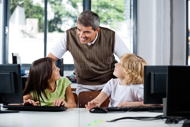 Teacher Assisting Schoolchildren In Using Desktop stock photos