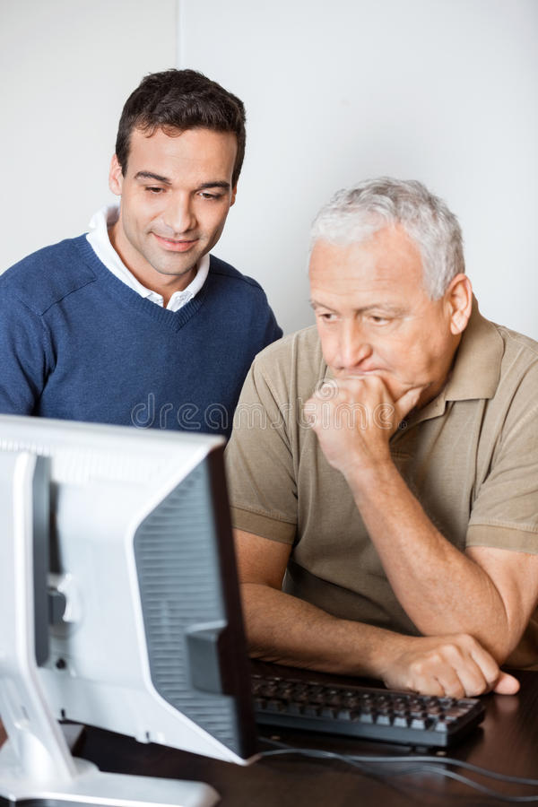 Teacher Assisting Senior Student In Computer Class stock photo