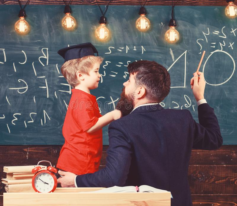 Teacher with beard, father teaches little son in classroom, chalkboard on background. Instructive conversation concept stock image