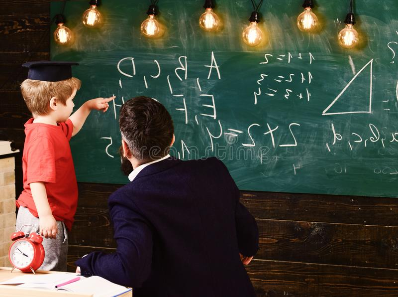 Teacher with beard, father teaches little son in classroom, chalkboard on background. Prodigy child concept. Boy, child stock photos
