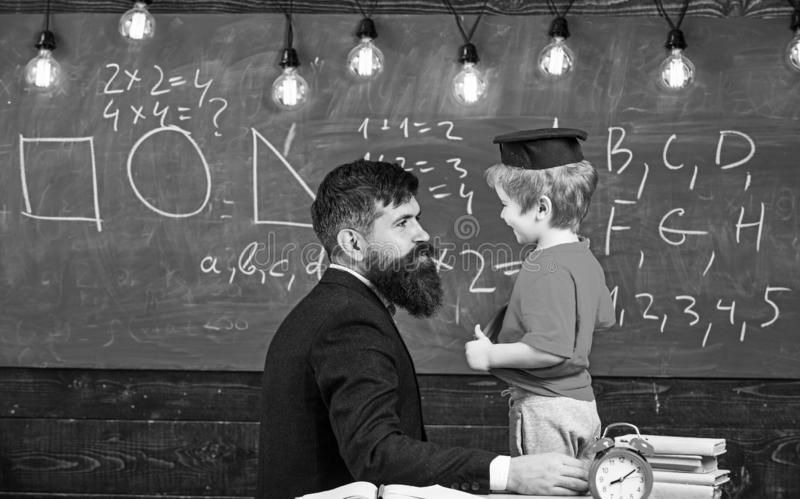 Teacher with beard, father teaches little son in classroom, chalkboard on background. School break concept. Boy, child royalty free stock photography