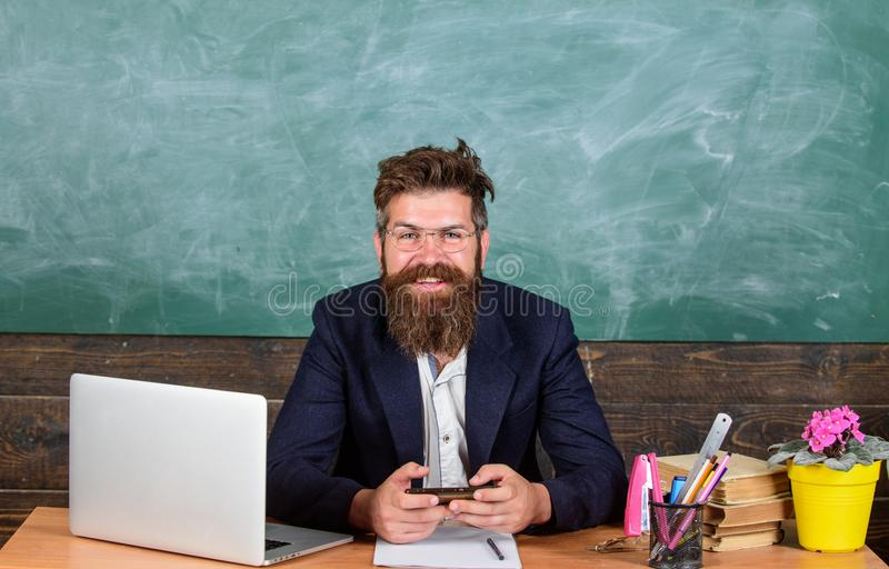 Teacher bearded hipster with eyeglasses sit in classroom chalkboard background. Teacher sit at desk with laptop. Back to stock images