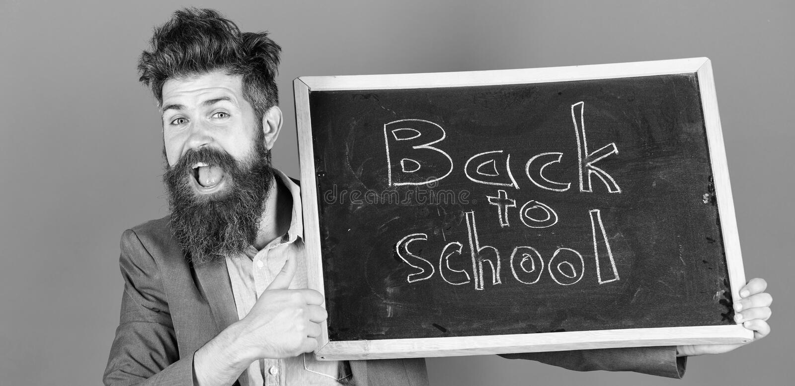 Teacher bearded man holds blackboard with inscription back to school blue background. Beginning of new school year gives. Us new opportunities. Teacher informs stock photos