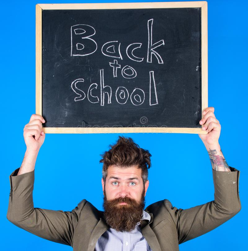Teacher bearded man holds blackboard with inscription back to school blue background. Teacher with tousled hair. Stressful about school year beginning. Teaching royalty free stock images