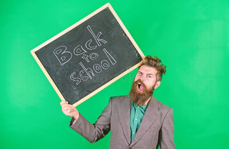 Teacher bearded man holds blackboard with inscription back to school green background. Keep working. Teacher with. Tousled hair stressful about school year royalty free stock images