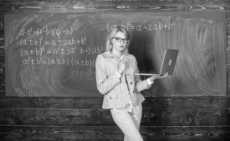 Teacher blonde woman with modern laptop surfing internet chalkboard background. School innovation. Distance education stock images
