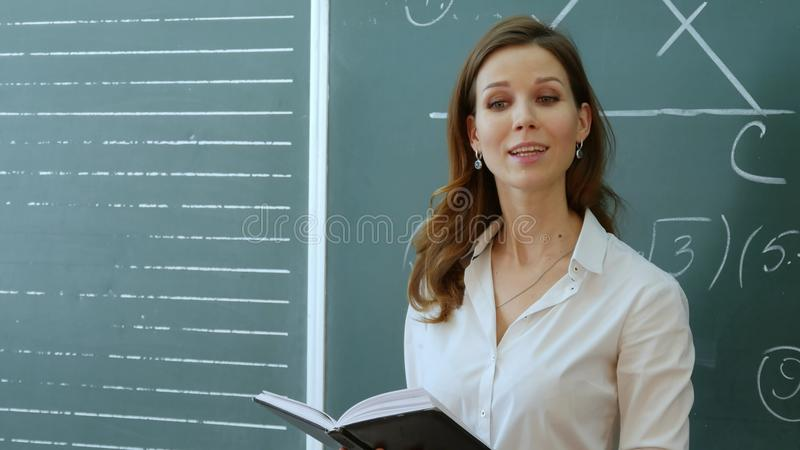 Teacher with book dictates in classroom at school. royalty free stock photography