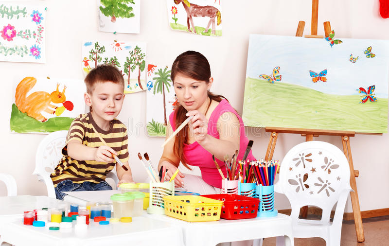 Teacher and boy learn draw in play room. royalty free stock photography