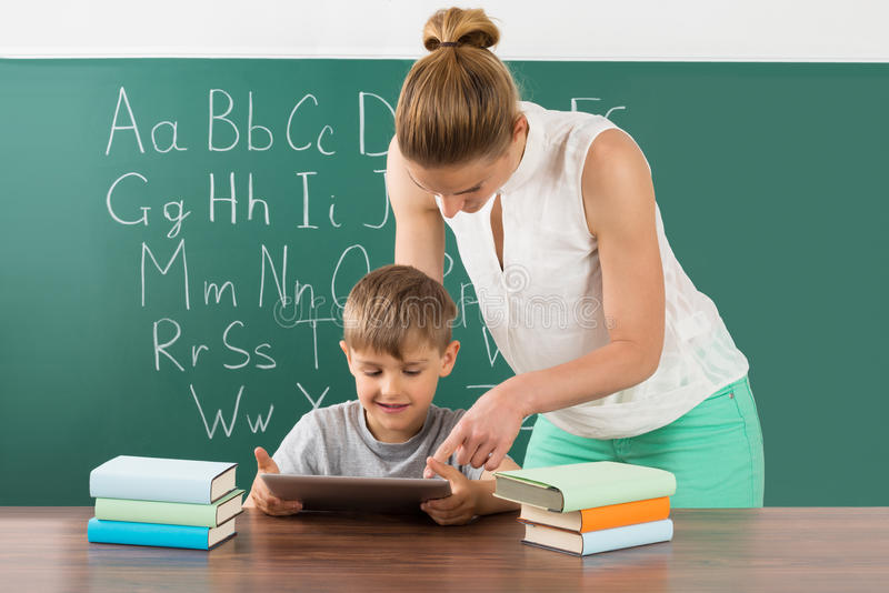 Teacher With Boy Using Digital Tablet In Classroom stock images