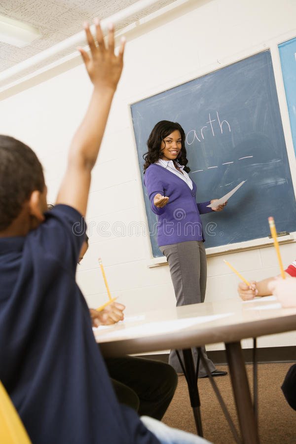 Teacher Calling on Student. Teacher smiling and pointing to student with hand raised. Vertical shot royalty free stock photo