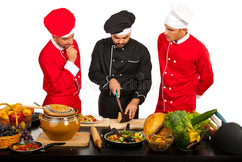 Teacher chef with students. Teacher chef teaching students in kitchen and cutting eggplant stock images