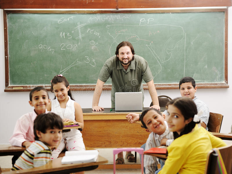 Teacher in classroom with his little student. Teacher in classroom with his little happy students stock photography