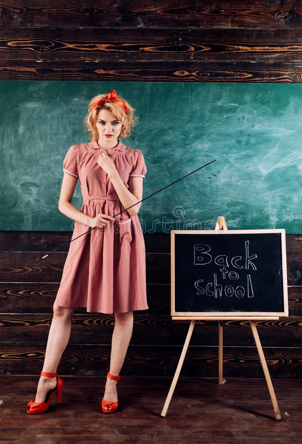 Teacher in classroom on school day. Pretty woman stand at blackboard on first school day stock photo
